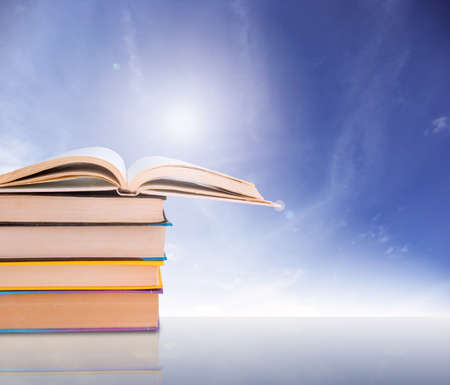 Stack of books on blue sky background photo