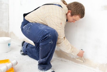 refinish: Man painting wall with small roller Stock Photo