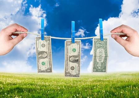 money laundering: Soldi sulla corda con la mano. tema di riciclaggio di denaro