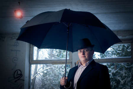 man with umbrella in old building. Conceptual creative idea image photo