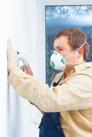 Young man builder polishing the wall. house environment theme photo