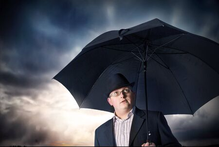 Businessman with umbrella and storm clouds background photo