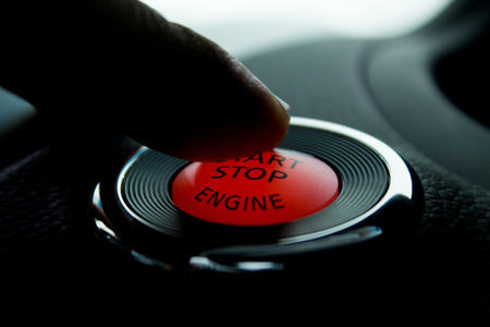 Finger on Push Start and stop engine botton in modern cars