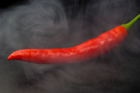 Red chilli feeling very hot and spicy with smoke on black background