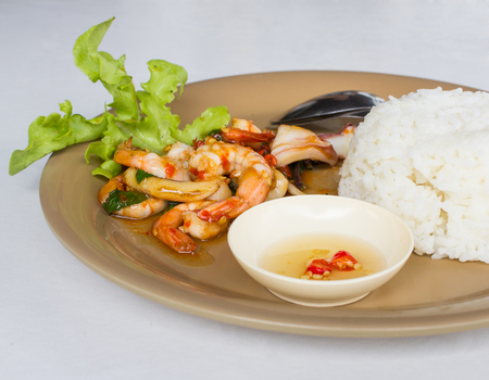 santa cena: Stir Fried Basil Seafood with rice on brown dish on white background Foto de archivo