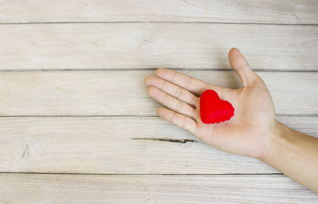 hand in hand: help,Heart in Hand on wood Stock Photo