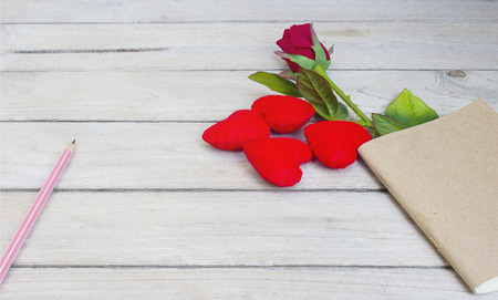 storytime: story love,Hearts, roses, pencil and book on wood Stock Photo