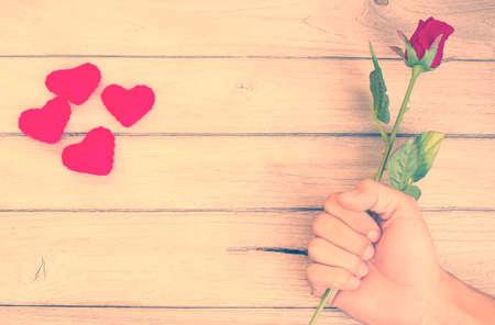 mujer con rosas: época El sentimiento de amor, Rose en la mano en la madera Foto de archivo