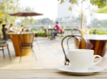coffee cup on wood table with blur coffee shop Background