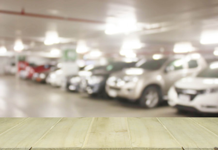 used car: soft focus wooden table with blur cars parking Stock Photo