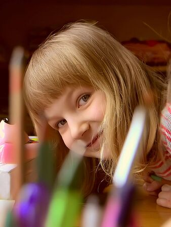 Smiling little girl with penñils and brushes.