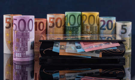 Several rolled hundred euro banknotes with casket in low key