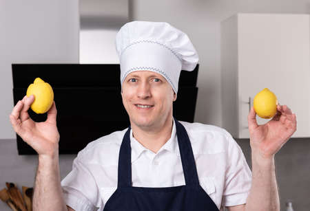 Surprised smiling male cook or baker holds lemons in his hands 免版税图像 - 157968323