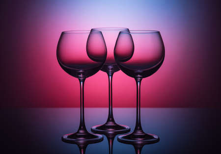 Three empty low key wine glasses against a colored background