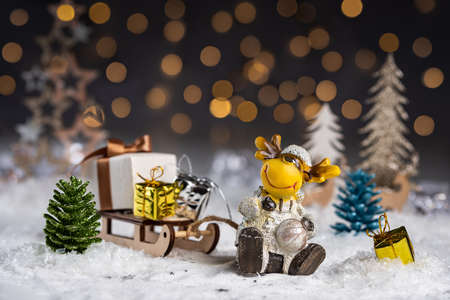 Christmas still life with toy deer sleigh and gifts in low key with bokeh