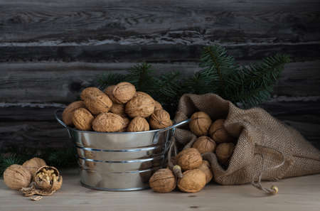 walnuts in a bowl and a sack on wooden table and a spruce branch 免版税图像