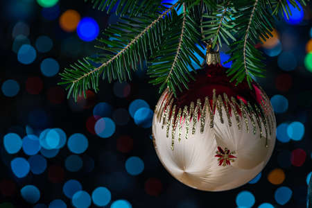 Light colored Christmas ball on a fir branch with bokeh in a low key at shallow depth of field
