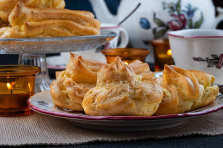 Cream puffs on a plate and serving plate with tea or coffee 免版税图像