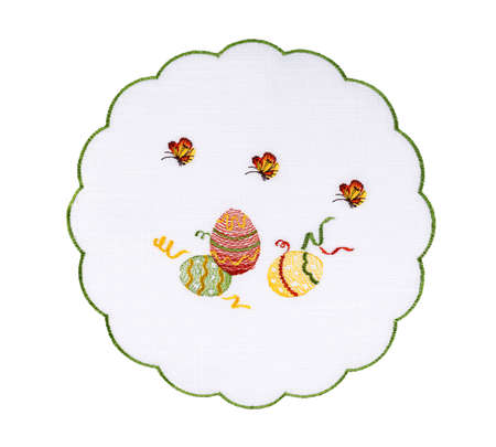 Round white cloth napkin with flounces and embroidered with threads Easter pattern in the form of festive decorated eggs and flying butterflies and trimmed with green border