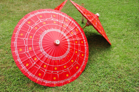 Red Handmade Painted Umbrellas on Yard in ChiangMai, Thailand photo