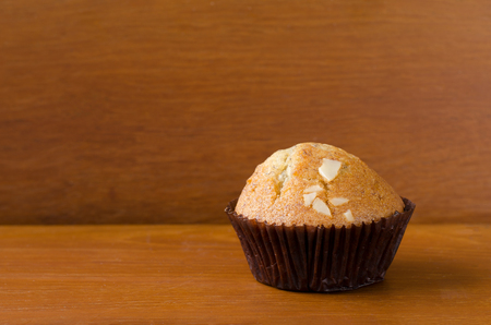 teakwood: A piece of delicious banana cup cake topped with sliced almond in dark brown paper cup over orange brown teakwood table with wooden background. Fresh baked cup cake with space, selective focus Stock Photo
