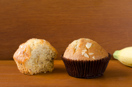 teakwood: Two pieces of delicious banana cup cake topped with sliced almond in dark brown paper cup over orange brown teakwood table with wooden background. Fresh baked cup cakes with space, selective focus.
