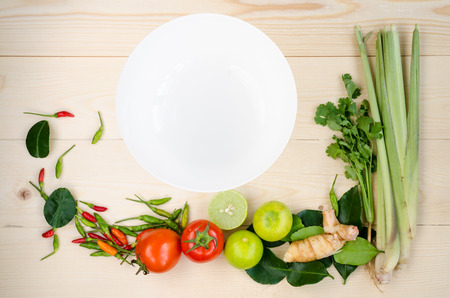 Flat lay of fresh Thai delicious spicy & sour Tom Yum dishs ingredients on wooden background of lemon grass, cilantro, galangal, kaffir lime leaves, limes, spicy bird peppers & white plate copy space