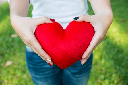 Asian lady hands holding red soft heart small pillow tightly to show her strong feeling of love on Valentines day, soft sunlight and selective focus Stock Photo