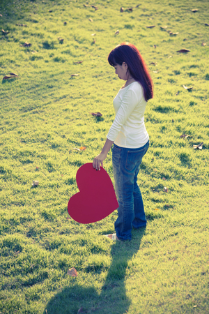 squeeze shape: Asian single lady standing on yard and holding red heart symbol sadly expressing her fail love on Valentines day with vintage tone