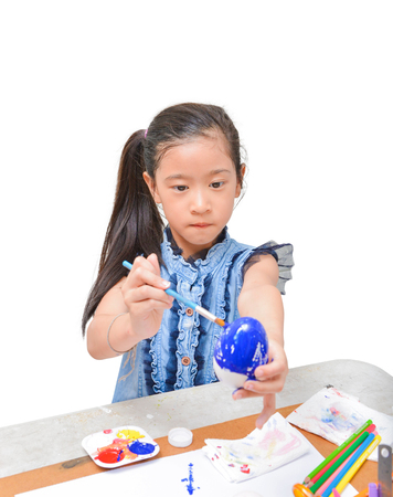 Asian girl kid concentrates on painting easter egg with brush in blue color isolated on white background (clipping path included)