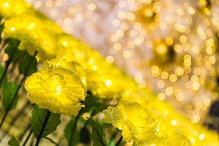 christmas grounds: Led lights of marigold fabric handmade flower garden decorated for celebrating Christmas season and new year 2017 shining at night time, selective focus with blur yellow bokeh background Stock Photo