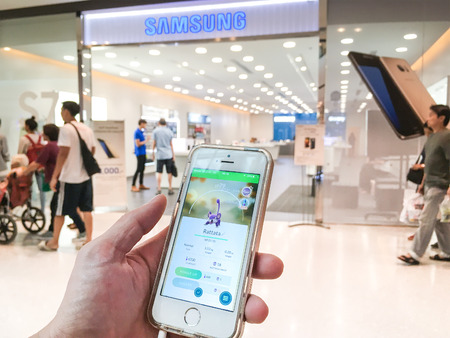 developed: BANGKOK, Thailand - August 8, 2016: A smartphone user play Pokemon Go in front of Sumsung mobile shop and catch Rattata monster. A free-to-play augmented reality mobile game developed by Niantic.