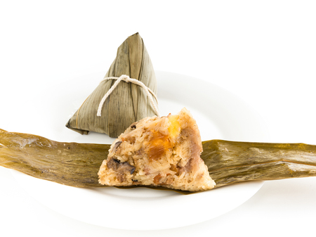 Chinese rice dumpling (Zongzi) stuffed with peanuts, mushroom, sweet mashed taro, marinated steamed pork, Ginkgo Biloba and salted egg yolk over bamboo leaf and white plate on white background Stock Photo