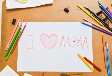 Sketch paper with a sentence I love mom surrounding by pencils, painting brush, tray of white, yellow, blue, red, green, yellow color and black clips over cork board in art class, top view Stock Photo