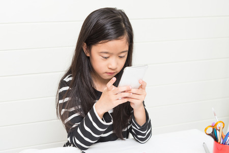 Cute asian girl kid playing smartphone happily to search video clip on the internet during her study time on light background