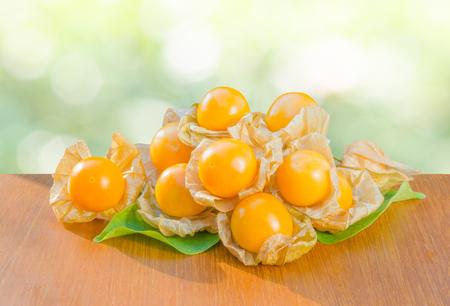 Verse pichuberry (Kaapse kruisbes), zeer heerlijke en gezonde bessen, uchuva op bruine houten tafel en bladeren met de natuur lichtgroene bokeh achtergrond in de tuin of boerderij