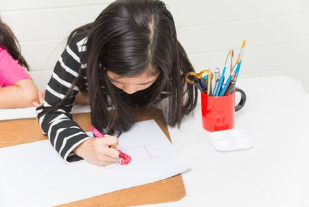 Asian girl kid concentrates on drawing a phrase I love by red colour crayon on white paper over table and light wall background with friends