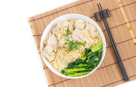 Wonton and egg noodle soup of Chinese Cantonese style for asian cuisine serving with Chinese cabbage (bog choy) and topped over bamboo plate mat isolated on white background, flat lay (top view)