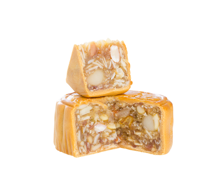 Moon cakes stuffed with five nuts; almond, walnut, white sesame, watermelon seeds, cashew nuts cut in half and small piece for bit size on stack isolated on white background (clipping path included) Stock Photo