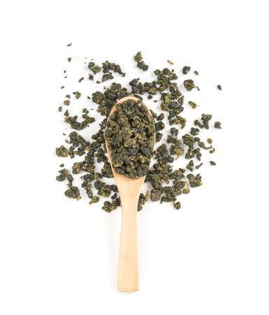 Fresh Tieguanyin Oolong tea on wooden spoon over white background for hot or cold drinks, top view (flat lay)
