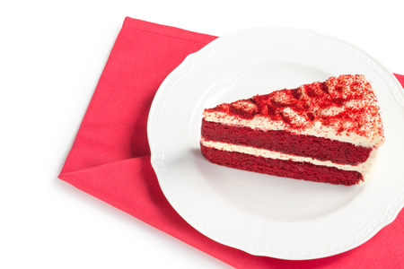 Red Velvet Cake sliced in piece on white plate over red placemat isolated on white background (Clipping path included) for celebrate Xmas season, Valentines day or special holiday events with copy space for text insertion Stock Photo