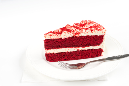 Red Velvet Cake sliced in piece on white plate with fork on white background for celebrate Xmas season, Valentines day, birthday or special holiday events Stock Photo