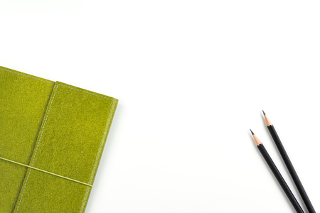Recycled paper notebook in green colour and two black pencils over white background with copy space for text insertion, green concept environment for saving earth