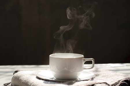 Hot black coffee in white ceramic cup and saucer on cozy wool scarf with nice steam warm sunlight in morning and copy space for text, wording insertion over dark grey background, hot beverage for winter concept