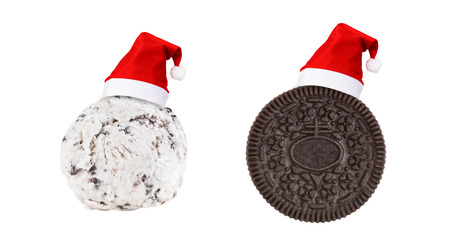 Santa Claus red hat on cookie and cream ice cream and cookie sandwich in piece isolated on white background (Clipping path included) to celebrate Christmas holiday season, new year party or special event Stock Photo
