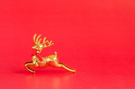 Gold reindeer over vivid red Christmas background with copy space for text, logo or product insertion, happy new year and holiday season concept