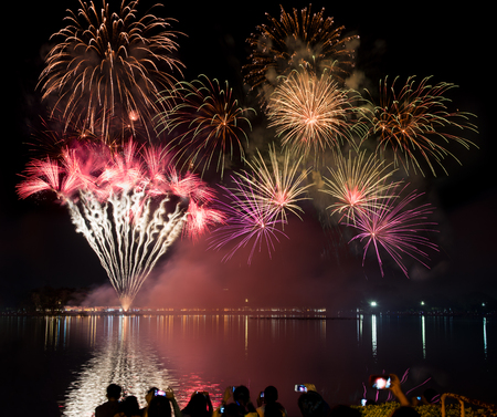 Fireworks in white, red, gold and green over river, lake or ocean beach at night for celebrating Happy New Year eve or special holidays with crowd taking photos, recording or shooting video clips
