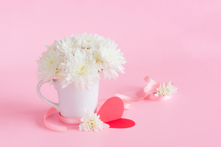 White Chrysanthemum flowers in ceramic white cup on pink lovely background with light pink bow, red heart paper card for love message and copy space for sweet Valentines day celebration text concept