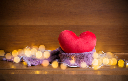 Red soft heart pillow with violet purple warm scarf and blurry warm white yellow light over dark brown wooden background with copy space for text decoration or insertion, love Valentines day concept Stock Photo