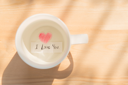 White coffee cup with paper cut in heart shape painted with red pencil and I love you in black on wood background under sunlight showing love relation concept on Valentines day or wedding celebration Banco de Imagens